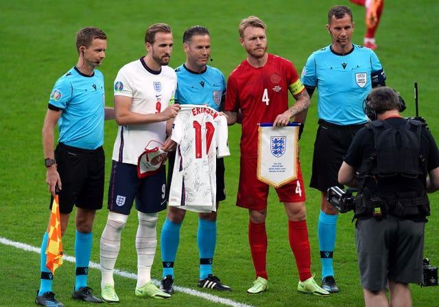 England captain Harry Kane and Denmark captain Simon Kjaer swap pennants and a signed Christian Eriksen shirt in tribute to the Denmark midfielder who suffered a cardiac arrest earlier in the tournament