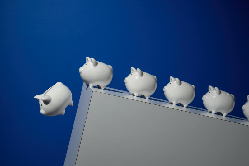 6 white piggy banks on inclined white surface, one falling over the edge, blue background