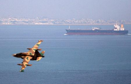 An Iranian military fighter plane flies past an oil tanker during naval manoeuvres in the Gulf and Sea of Oman