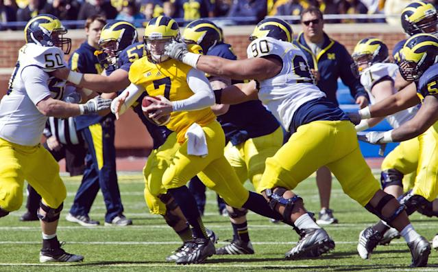 Michigan quarterback Shane Morris (7) has his face mask pulled by defensive tackle Bryan Mone (90) during the football team's annual spring game on Saturday, April 5, 2014, in Ann Arbor, Mich. (AP Photo/Tony Ding)