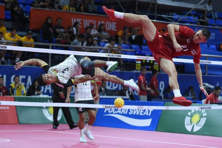 Thailand's Jirasak Pakebuangoen (R) attempts a block against Myanmar's Aung Myo Naing during the sepak takraw match at the SEA Games