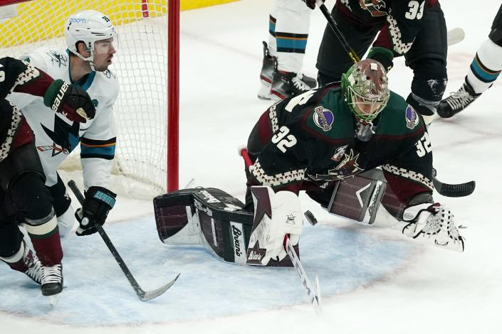 Arizona Coyotes goaltender Antti Raanta (32) dives to make a save on a shot by San Jose Sharks center Logan Couture (39) during the first period of an NHL hockey game Saturday, Jan. 16, 2021, in Glendale, Ariz. (AP Photo/Ross D. Franklin)
