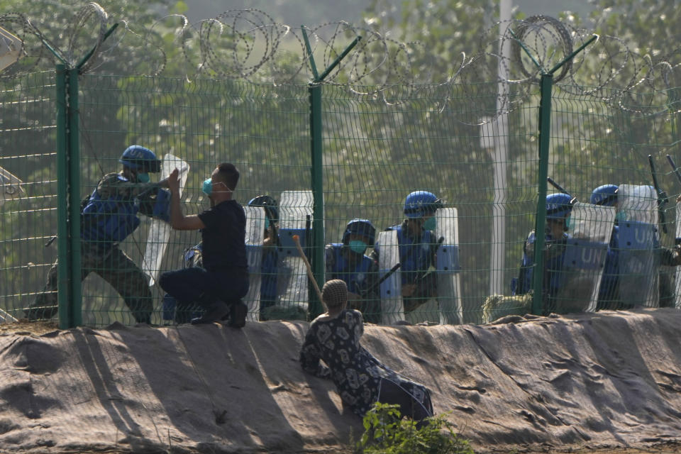 Participants in the role of refugees escaping fighting plead for help outside a United Nations compound during the Shared Destiny 2021 drill at the Queshan Peacekeeping Operation training base in Queshan County in central China's Henan province Wednesday, Sept. 15, 2021. Peacekeeping troops from China, Thailand, Mongolia and Pakistan took part in the 10 days long exercise that field reconnaissance, armed escort, response to terrorist attacks, medical evacuation and epidemic control. (AP Photo/Ng Han Guan)