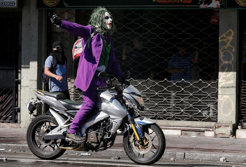 A protester dressed as a joker rides a motocycle during a protest against Chile's government in Valparaiso, Chile on Oct. 28, 2019. (Photo: Rodrigo Garrido/Reuters)