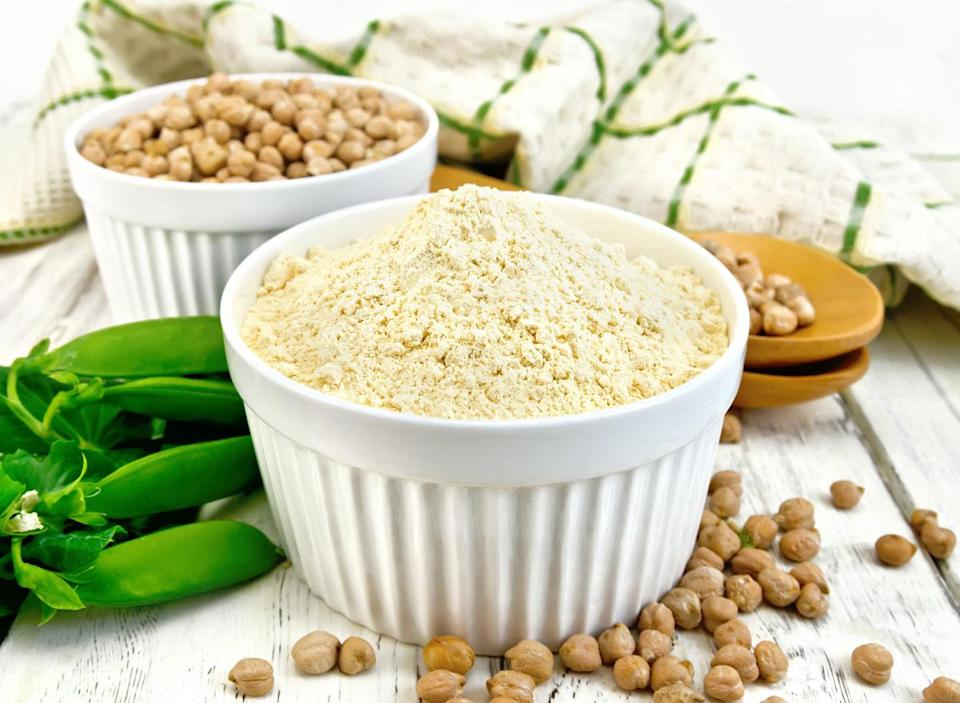 Vegan pea protein powder in white ramekin next to whole pea pod