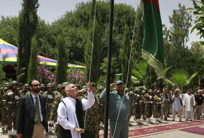 Ashraf Ghani, head of the Transition Commission raises Afghanistan's flag during the transfer of authority  in Mehterlam, Laghman province, east of Kabul, Afghanistan on Tuesday, July 19, 2011. NATO handed over responsibility for the security of the capital of an eastern province to Afghan forces Tuesday, the latest step in a transition process that will lead to the withdrawal of all foreign combat troops by the end of 2014. Ghani, a government official who is leading the transition effort, acknowledged that the security situation in the east had deteriorated even as it improved in the south. (AP Photo/Musadeq Sadeq)
