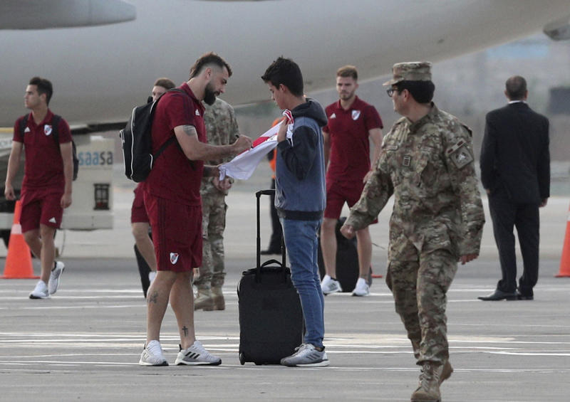 Lucas Pratto of Argentina's River Plate, signs a fan's t-shirt, after his team arrived at the military airport Grupo Aereo 8, in Lima, Peru, Wednesday, Nov. 20, 2019. The team will play Brazil's Flamengo on Saturday's Copa Libertadores final. (AP Photo/Martin Mejia)