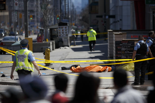 <p>A tarp lays on top of a body on Yonge St. at Finch Ave. after a van plowed into pedestrians on April 23, 2018 in Toronto, Canada. A suspect is in custody after a white van collided with multiple pedestrians. (Photo: Cole Burston/Getty Images) </p>
