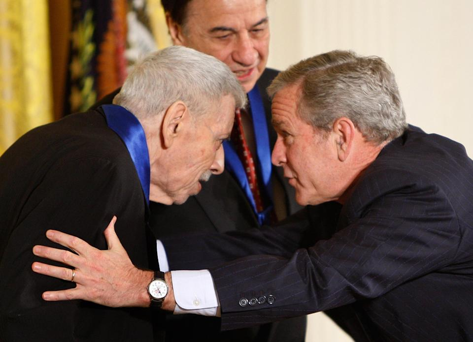"""FILE - In this Nov. 17,2008 file photo President George W. Bush, right, greets song writer Robert Sherman, in the East Room of the White House in Washington, as he presents him with the 2008 National Medals of Arts. Songwriter Sherman, who wrote the tongue-twisting """"Supercalifragilisticexpialidocious"""" and other enduring songs for Disney classics, has died. He was 86. (AP Photo/Ron Edmonds,File)"""