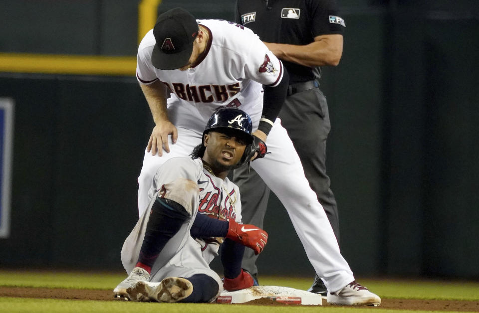 Atlanta Braves' Ozzie Albies, bottom, reacts after being tagged out by Arizona Diamondbacks second baseman Josh VanMeter, top, during the fifth inning of a baseball game Thursday, Sept 23, 2021, in Phoenix. (AP Photo/Darryl Webb)