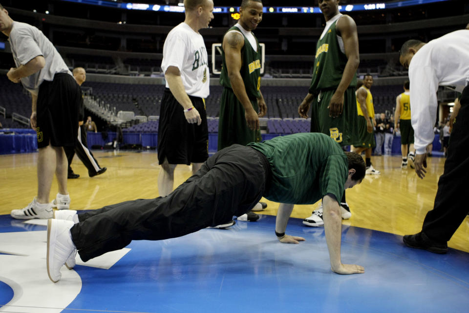 Baylor head coach Scott Drew does five push-ups at center court after a successful team practice at the Verizon Center in Washington, Wednesday, March 19, 2008 in preparation for the NCAA first round West Regional basketball game. Looking on are Baylor players Curtis Jerrells, center, and Fred Ellis, right. (AP Photos/Pablo Martinez Monsivais)