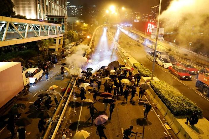 Anti-government demonstrators take cover during clashes with police near the Hong Kong Polytechnic University (PolyU) in Hong Kong