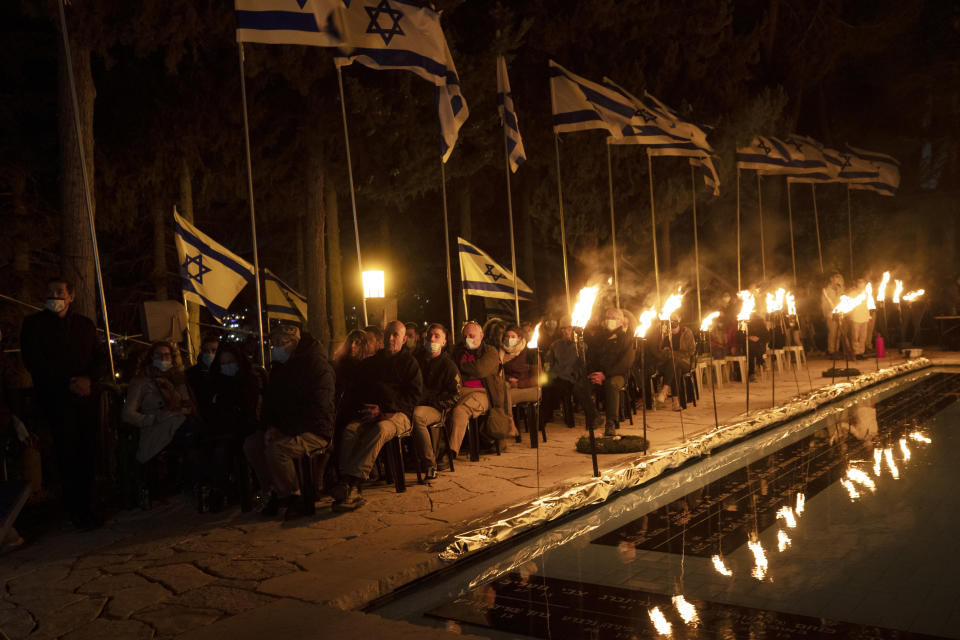 Guests are illuminated by torches during a Memorial Day ceremony commemorating fallen soldiers, at the military cemetery at Mount Herzl in Jerusalem, Tuesday, April 13, 2021. (AP Photo/Maya Alleruzzo)