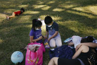 Regina Cel, left, and brother Leandro shell peanuts with their masks on next to their parents at a park during the coronavirus pandemic, in the Westlake neighborhood of Los Angeles, Thursday, May 21, 2020. While most of California is welcoming a slight return toward normal this holiday weekend, Los Angeles will not be joining the party. The nation's largest county is not planning to reopen more widely until the next summer holiday, July 4th, because of a disproportionately large share of the state's coronavirus cases and deaths that have hampered the county's ability to rebound and meet strict criteria to get more people back to work. (AP Photo/Jae C. Hong)