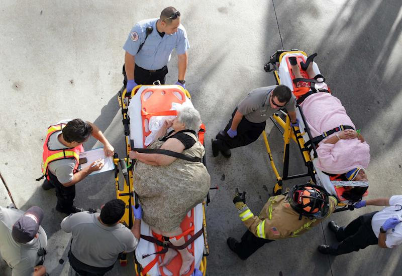 Emergency personnel attend to injured passengers after a bus accident at Miami International Airport on Saturday, Dec. 1, 2012 in Miami. Officials say a bus has hit an overpass, killing at least one person and injuring more than two-dozen people on board. Airport spokesman Greg Chin says the large, white bus hit the overpass going into the airport's arrivals section on Saturday morning. The bus was going about 20 mph when it clipped the roof entrance. (AP Photo/El Nuevo Herald, Roberto Koltun)