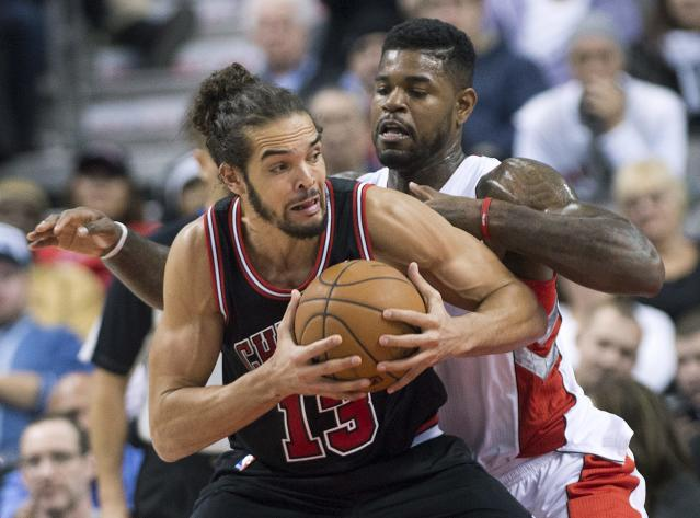Toronto Raptors forward Amir Johnson, back, guards against Chicago Bulls forward Joakim Noah, front, during first-half NBA basketball game action in Toronto, Friday, Nov. 15, 2013. (AP Photo/The Canadian Press, Nathan Denette)