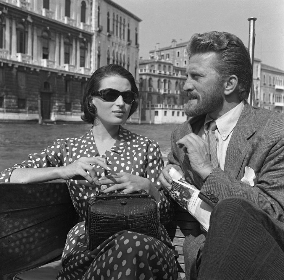 <p>American actor Kirk Douglas sits on a water taxi next to Italian actress Silvana Mangano on the Canal Grande in Venice, Italy, circa 1953.</p>