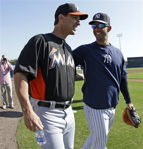 Miami Marlins hitting coach Tino Martinez, left, chats with former Yankees catcher and current Yankees guest instructor Jorge Posada on the field before a spring training baseball game between the Marlins and the Yankees in Tampa, Fla., Friday, March 15, 2013. (AP Photo/Kathy Willens)
