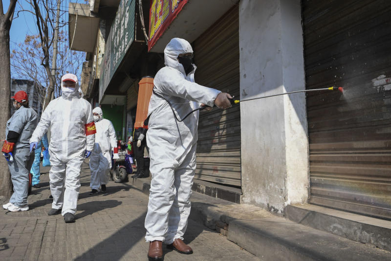 In this photo released by Xinhua News Agency, workers disinfect closed shop lots following the coronavirus outbreak, in Jiang'an District of Wuhan in central China's Hubei Province, Monday, Feb. 10, 2020. Mainland China has reported another rise in cases of the new virus after a sharp decline the previous day, while the number of deaths grow over 900, with at least two more outside the country. (Cheng Min/Xinhua via AP)