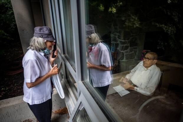 Veronica DeLorme visits her father, Paul DeLorme, through a window ahead of his 100th birthday at the Weinberg Residence in Vancouver in July 2020. The new guidelines will allow for hugs.