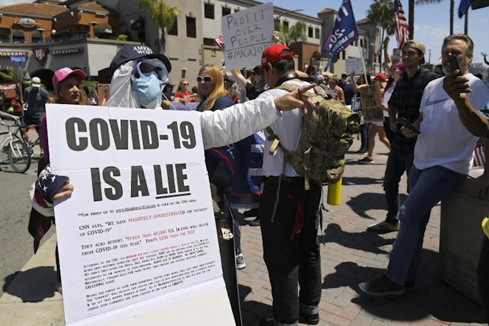 """Protesters, including anti-vaccine activists, demonstrate against stay-at-home orders, which were implemented to combat the coronavirus pandemic, on April 17, 2020, in Huntington Beach. <span class=""""copyright"""">(Mark J. Terrill / Associated Press)</span>"""