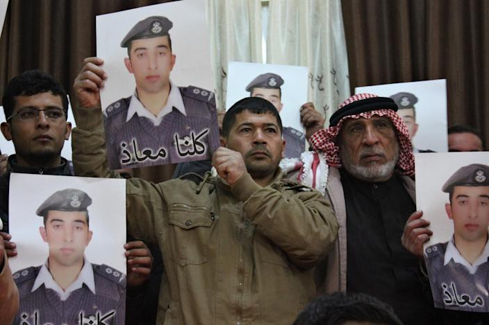 """Relatives of Islamic State captive Jordanian pilot Muath al-Kasaesbeh hold his poster as they take part in a rally in his support at the family's headquarters in the city of Karak, January 31, 2015. The words on the portrait reads, """"We are all Muath."""" REUTERS/Stringer (JORDAN - Tags: POLITICS CIVIL UNREST TPX IMAGES OF THE DAY)"""