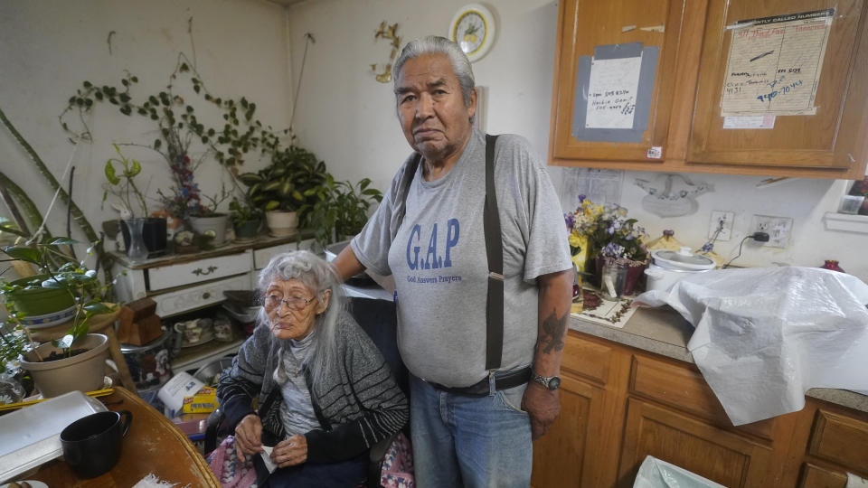 """Arthur John, 82, a retired trapper, and his wife of 62 years, 99-year-old Isabel pose for a photograph at their home Thursday, Sept. 23, 2021, in Tanacross, Alaska. Arthur John spent nearly 30 days at in the hospital with COVID, dropping about 40 pounds during his stay. """"It makes me weak and can't work like before,"""" the village elder said. """"There's so much it took off me and I just wish for working."""" (AP Photo/Rick Bowmer)"""