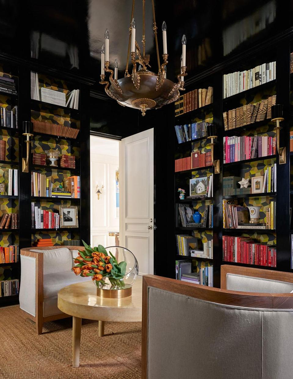 """<p>When designing a small space, Interior designer <a href=""""https://www.jeanliudesign.com/"""" rel=""""nofollow noopener"""" target=""""_blank"""" data-ylk=""""slk:Jean Liu"""" class=""""link rapid-noclick-resp"""">Jean Liu</a> encourages clients to use a dark paint color like <a href=""""https://www.sherwin-williams.com/homeowners/products/SW6258-tricorn-black"""" rel=""""nofollow noopener"""" target=""""_blank"""" data-ylk=""""slk:Tricorn Black"""" class=""""link rapid-noclick-resp"""">Tricorn Black</a> by Sherwin Williams. """"Contrary to conventional thinking, painting a room dark and minimizing the delineation between the walls, the ceilings, and the baseboards allows the room to appear larger and taller than it may actually be,"""" she says. """"We love the effect it gave this small library.""""</p>"""