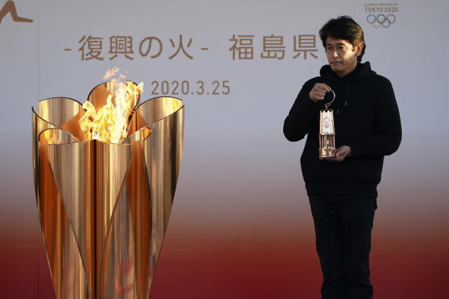 """An official holds a lantern containing the Olympic Flame at the end of a flame display ceremony in Iwaki, northern Japan, Wednesday, March 25, 2020. IOC President Thomas Bach has agreed """"100%"""" to a proposal of postponing the Tokyo Olympics for about one year until 2021 because of the coronavirus outbreak. (AP Photo/Eugene Hoshiko)"""