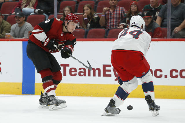 Arizona Coyotes left wing Christian Dvorak (18) shoots in front of Columbus Blue Jackets defenseman Vladislav Gavrikov in the second period during an NHL hockey game, Thursday, Nov. 7, 2019, in Glendale, Ariz. (AP Photo/Rick Scuteri)