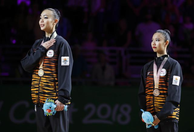 Rhythmic Gymnastics - Gold Coast 2018 Commonwealth Games - Individual Ribbon Final - Coomera Indoor Sports Centre - Gold Coast, Australia - April 13, 2018. Gold medallist Kwan Dict Weng of Malaysia and bronze medallist Koi Sie Yan of Malaysia listen to their national anthem. REUTERS/David Gray