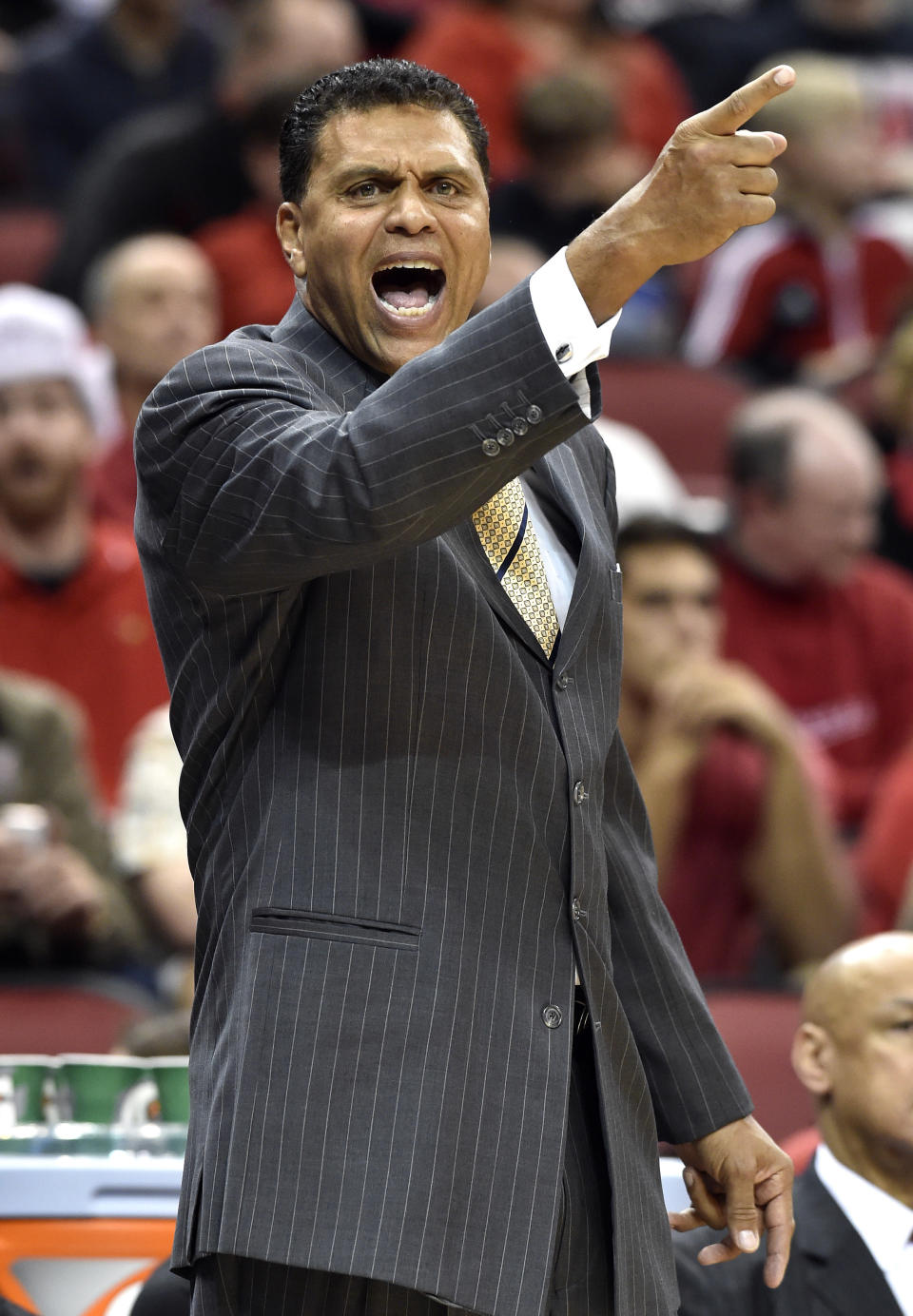 Cal State Northridge coach Reggie Theus shouts instructions to his team during the first half of an NCAA college basketball game against Louisville, Tuesday Dec. 23, 2014, in Louisville, Ky. (AP Photo/Timothy D. Easley)