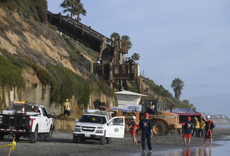 FILE - In this Friday, Aug. 2, 2019 lifeguards and search and rescue personnel work at the site of a cliff collapse at a popular beach in Encinitas, Calif. Three family members enjoying a day at a San Diego area beach were killed Friday when a huge slab of the cliff above plunged on to the sand. The collapse has raised questions about the stability of bluffs along California's 1,000-mile (1,600-kilometer) coast. (AP Photo/Denis Poroy,File)