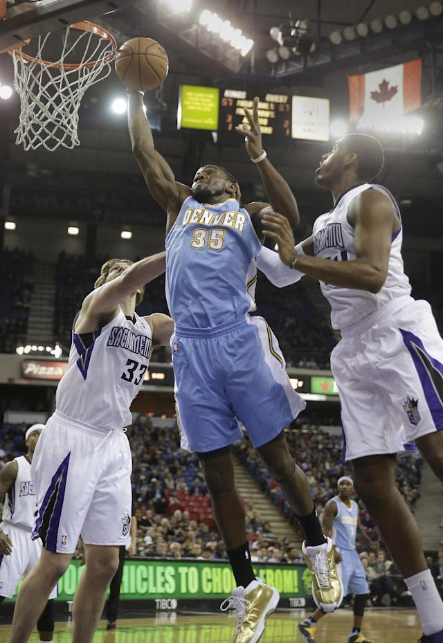 Denver Nuggets forward Kenneth Faried, center, grabs a rebound between Sacramento Kings' Aaron Gray, left, and Jason Thompson during the first quarter of an NBA basketball game in Sacramento, Calif., Sunday, Jan. 26, 2014. (AP Photo/Rich Pedroncelli)