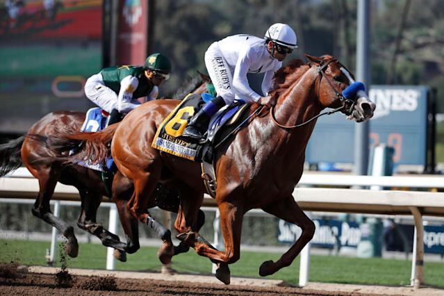 Justify, ridden by Mike Smith, gallops past Bolt d'Oro, left, with jockey Javier Castellano, during the Santa Anita Derby horse race at Santa Anita on Saturday, April 7, 2018, in Arcadia, Calif. (AP)