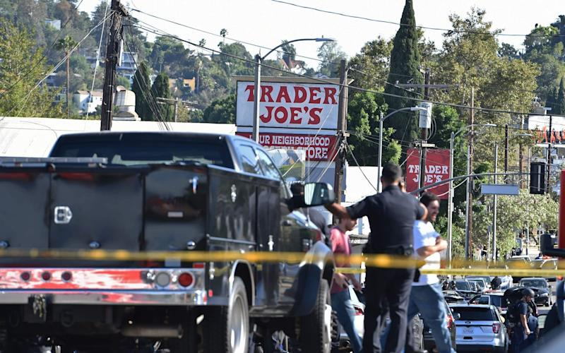 Police officers guard a supermarket with a barricaded suspect in Silverlake, Los Angeles - AFP