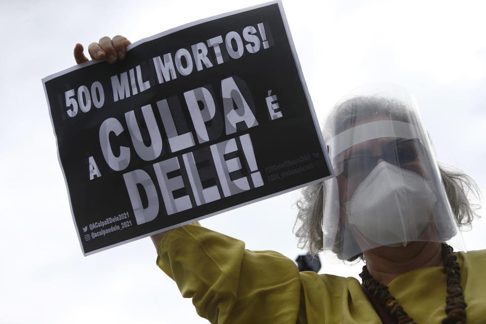 """A demonstrator holds a sign with a message that reads in Portuguese; """"500K deaths! His fault!"""" during a demonstration against Brazilian President Jair Bolsonaro's handling of the coronavirus pandemic and economic policies protesters say harm the interests of the poor and working class, in Rio de Janeiro, Brazil, Saturday, June 19, 2021. Brazil is approaching an official COVID-19 death toll of 500,000 — second-highest in the world. (AP Photo/Bruna Prado)"""