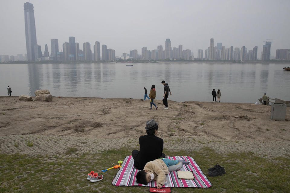 """A child wearing a mask rests along the Yangtze River on April 5, 2020, in Wuhan in central China's Hubei province just days before the lifting of the city's 76-day coronavirus lockdown. Associated Press photographer Ng Han Guan says of the photo: """"Personally the photo summed up my feelings being in the city which was unceremoniously shut down and residents forced into a comatose state of inactivity that somehow became normalized."""" Though the riverbank scene is Idyllic, he says, """"in the background a slumbering city skyline is ready to hum back to life."""" (AP Photo/Ng Han Guan)"""