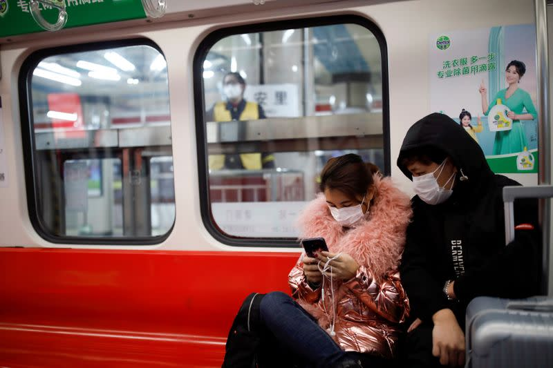 FILE PHOTO: People wearing masks travel in the subway, as the country is hit by an outbreak of the new coronavirus, in Beijing