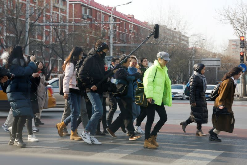 Teresa Xu is surrounded by journalists as she crosses a road near Chaoyang People's Court after a court hearing in Beijing