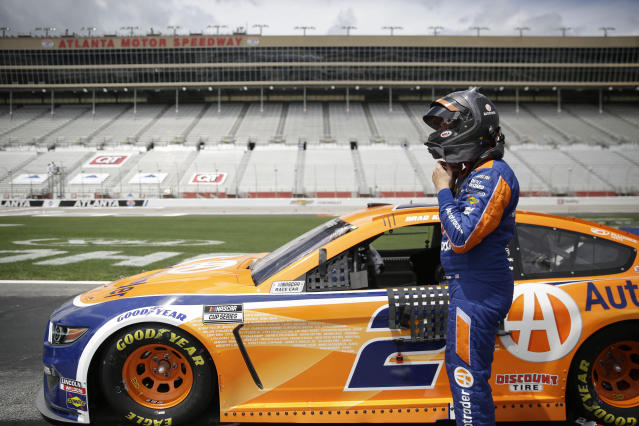 Brad Keselowski (2) puts on a helmet before a NASCAR Cup Series auto race at Atlanta Motor Speedway, Sunday, June 7, 2020, in Hampton, Ga. (AP Photo/Brynn Anderson)