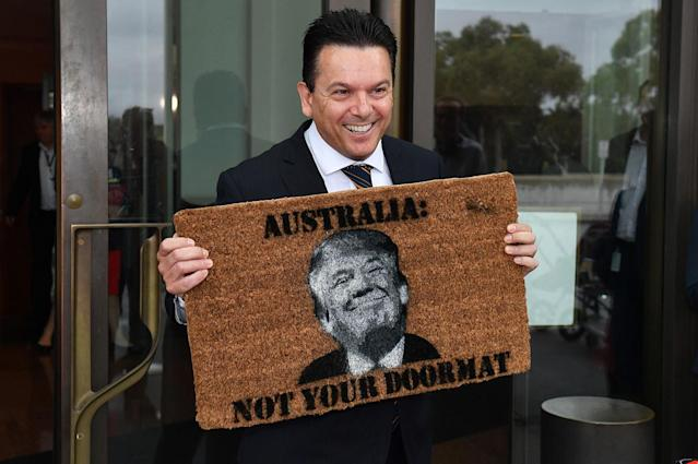 <p>Leader of the Nick Xenophon Team, Australian Senator Nick Xenophon arrives at the Senate entrance holding a novelty doormat depicting US President Donald Trump and reading 'Australia: Not Your Doormat,' at Parliament House in Canberra, Australian Capital Territory, Australia, Feb. 7, 2017. (Photo: Mick Tsikas/EPA) </p>