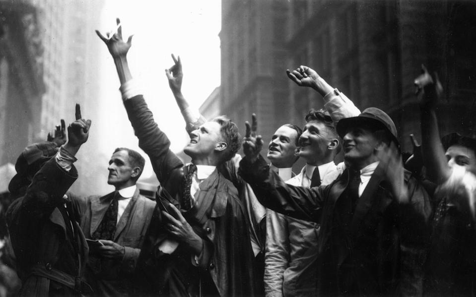 Curb Market traders gesture with their hands to trade stocks on Wall Street, in downtown Manhattan. (The Market was for stocks that were unlisted on the New York Stock Exchange.)