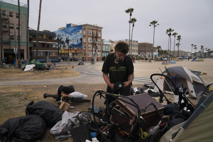 Jeremy Minney, a 43-year-old homeless man, sorts through his belongings in a homeless encampment set up along the boardwalk in the Venice neighborhood of Los Angeles, Tuesday, June 29, 2021. The proliferation of homeless encampments on Venice Beach has sparked an outcry from residents and created a political spat among Los Angeles leaders. (AP Photo/Jae C. Hong)