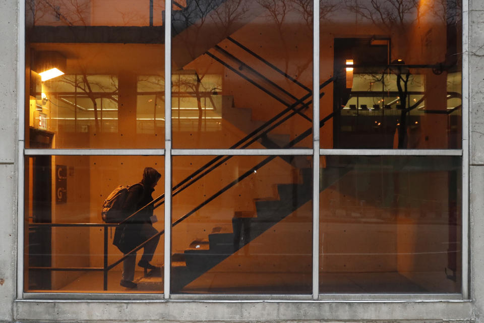 In this Wednesday, April 22, 2020, RUSH Hospital respiratory therapist Jumana Azam heads to a garage walkway before starting her early morning shift at the hospital in Chicago. (AP Photo/Charles Rex Arbogast)