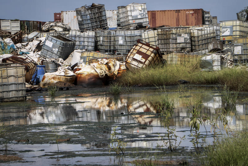 "In this photo taken Monday, Oct. 1, 2018, containers used for hazardous chemicals lie exposed and piled up at a junkyard run by the Chinese-led Dar Petroleum Operating Company in Gumry, near Paloch, in South Sudan. The oil industry in South Sudan has left a landscape pocked with hundreds of open waste pits with the water and soil contaminated with toxic chemicals and heavy metals, and accounts of ""alarming"" birth defects, miscarriages and other health problems, according to four environmental reports obtained by The Associated Press. (AP Photo/Sam Mednick)"
