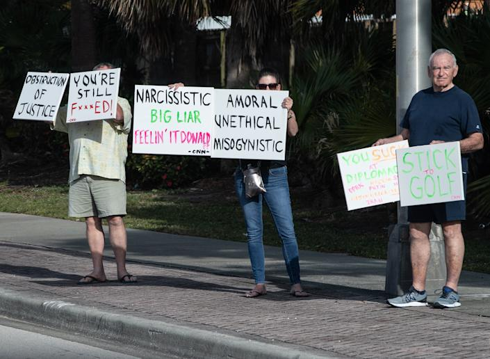 Protesters hold signs as President Donald Trump's motorcade makes its way to the Trump International Golf Club in West Palm Beach, Florida, on April 20, 2019.  (Photo: NICHOLAS KAMM via Getty Images)