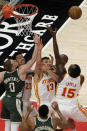 The Atlanta Hawks and the Milwaukee Bucks fight for a rebound during first half of an NBA basketball game on Sunday, April 25, 2021, in Atlanta. (AP Photo/Ben Gray)