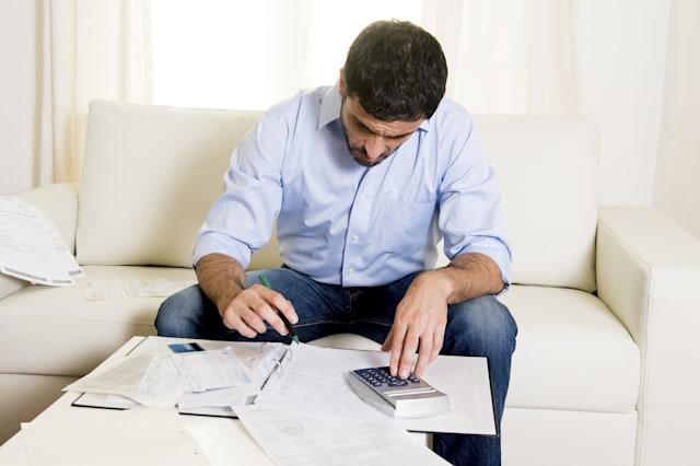 handsome latin business man worried paying bills on couch