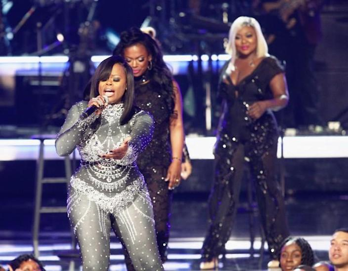 Three women performing onstage in sparkly outfits